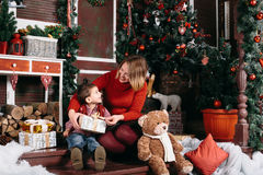 Loving Christmas traditions. Mother giving a present to her little son. Beautiful women gives a gift to his son. Boy and women smile at each other Stock Photography