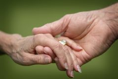 Closeup of a Married Senior Citizens Holding Hands. A loving closeup scene of a senior married couple holding hands with wedding rings Royalty Free Stock Photography