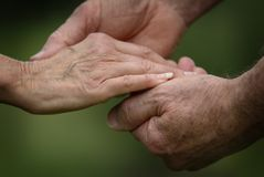 Closeup of a Married Senior Citizens Holding Hands. A loving closeup scene of a senior married couple holding hands with wedding rings Stock Photos