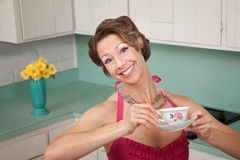 Loving Coffee. Woman with a big smile enjoys a cup of coffee in her kitchen Stock Photo
