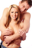 Loving couple. A attractive loving couple topless and cuddling in front of a white background stock images
