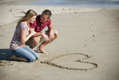 Loving couple. At the beach drawing a heart in the sand Royalty Free Stock Photo