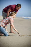 Loving couple. At the beach drawing a heart in the sand Royalty Free Stock Images