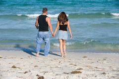 Loving Couple. Brunette Couple Holding Hands walking at the beach Stock Photos