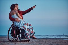 Free Loving Couple, A Woman Sits On Her Husband`s Lap, Resting On A Beach Against A Background Of A Bright Dawn. Royalty Free Stock Photos - 114982358
