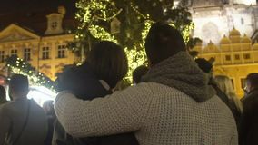 Loving couple admiring beautiful view of decorated luminous Christmas Tree. Stock footage stock video
