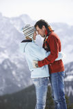 Loving Couple Against Snow Covered Mountain. Side view of a loving couple standing face to face against snow covered mountain Royalty Free Stock Photo