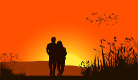 Loving couple against a sunset sky Stock Image