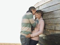 Loving Couple Against Wooden Hull Of Boat Stock Images