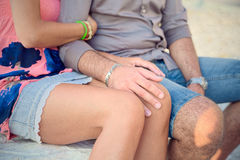 Loving couple arm, sitting on a bench on top of a marble quarry in Carrara, he strokes her knee. Stock Image