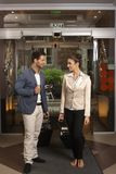 Loving couple arriving at hotel lobby. Young loving couple arriving at hotel lobby with suitcases, smiling Stock Image