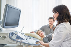 Loving couple attending doctor for pregnancy ultra sound procedu royalty free stock photo