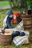 Loving couple in autumn garden. Loving couple sitting in the autumn garden Royalty Free Stock Photography
