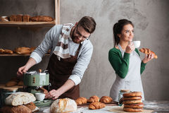 Loving couple bakers eating croissants drinking coffee Royalty Free Stock Images