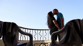 Loving Couple on the Balcony in Sunglasses Hugging and Kissing With a View of the Sky. Loving Couple on the Balcony in Sunglasses With a View of the Sky, have stock footage
