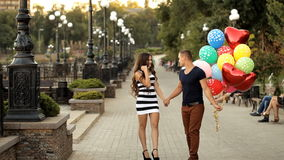Loving couple with balloons walking along the waterfront stock footage