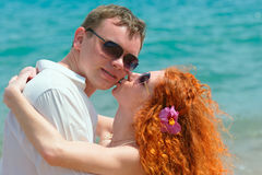 Loving couple at the beach. Handsome men posing with his redhead girlfriend Stock Images