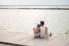 Loving couple on the beach hugging while looking at sea. Loving couple on the beach hugging while sitting and looking at the sea Stock Photo