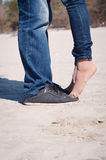 Loving couple on the beach. In jeans and black shoes Stock Photography