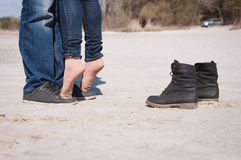 Loving couple on the beach. In jeans and black shoes Stock Photos