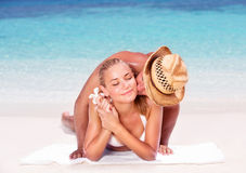Loving couple on the beach. Lying down on sandy coast and kissing, enjoying honeymoon vacation, summer vacation concept Royalty Free Stock Photography
