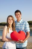 Loving couple at the beach. With red heart Royalty Free Stock Photo