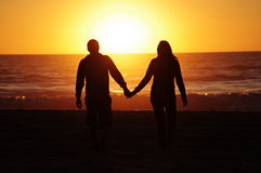 Loving couple beach sunset Stock Photos