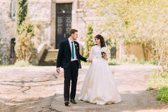 Loving couple, beautiful bride and handsome groom, strolling in park. Old vintage building at background Royalty Free Stock Image