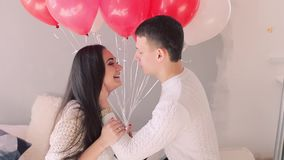 Loving couple on the bed with balloons stock video