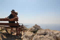 Loving couple on a bench at top of the cape of Greco Stock Photography