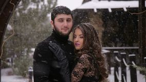 Bride in a black dress. Gothic wedding. Winter. A loving couple in black clothes stands embracing against the background of a stone old mansion with a heavy stock video footage