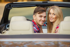 Loving couple in a black convertible in the park. Stock Image