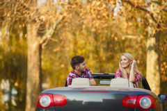 Loving couple in a black convertible in the park. Stock Images