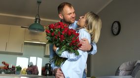 Loving couple with a bouquet of flowers in the kitchen. Newlyweds on Valentine`s Day cuddle at home.  stock video footage