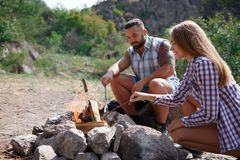 A loving couple bred a fire on a picnic in the forest to fry meat. A girl is kindling a fire in nature. Summer time Royalty Free Stock Image