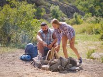A loving couple bred a fire on a picnic in the forest to fry meat. A girl is kindling a fire in nature. Summer time. A sweet girl helps her boyfriend to kindle a Royalty Free Stock Photo
