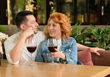 Loving couple in a cafe. A women with a young men at a table with a glass of wine Royalty Free Stock Photos