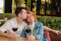 Loving couple in a cafe. A women with a young men at a table with a glass of wine Stock Photos