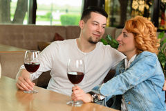 Loving couple in a cafe. A women with a young men at a table with a glass of wine Royalty Free Stock Image