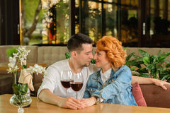 Loving couple in a cafe. A women with a young men at a table with a glass of wine Royalty Free Stock Photography