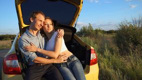Loving couple in car. Road Trip. A loving couple in a road trip. The guy and the girl are sitting in the open trunk of the car. They talk, kiss and hug. Stop stock video