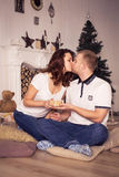 Loving couple celebrating christmas and new year at home sitting Royalty Free Stock Images