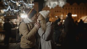 Loving couple celebrating xmas together at night market in Prague. Love, family, christmas, new year, holiday concept