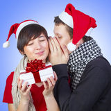 Loving couple with Christmas gift. Man talks secret to women with Christmas gift Royalty Free Stock Photo