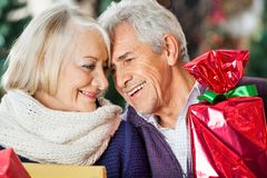 Loving Couple With Christmas Presents In Store Royalty Free Stock Image