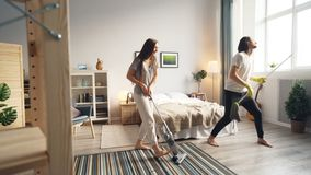 Loving couple cleaning floor with vacuum cleaner and mop dancing singing