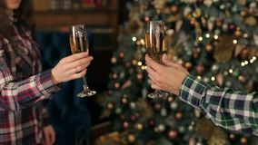 Glass of champagne near the Christmas tree. CU. Loving couple clink glasses of champagne on the background of the Christmas tree. The New year celebration. Close stock footage