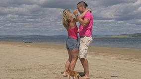 Loving couple on the coast, dancing. This is their love story. They hug and kiss. A man and a woman are happy and joyful. In the video dogs stock video footage