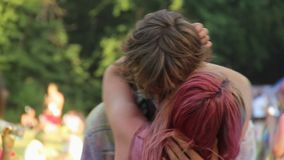 Loving couple colored with paint powder hugging and dancing at music festival. Stock footage stock video footage