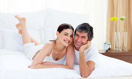 Loving couple cuddling lying on their bed. Portrait of a loving couple cuddling lying on their bed stock photo